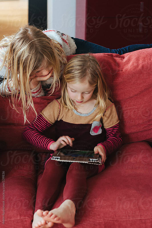 2 female children looking at a tablet device. by Helen Rushbrook for Stocksy United