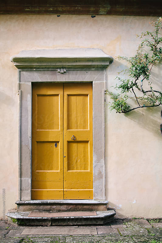a yellow door on a fresco wall in florence by Sarah Lalone for Stocksy United