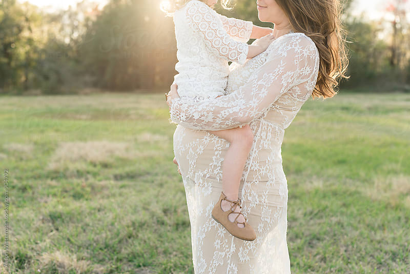 A Mother Holds Her Baby Girl On Her Pregnant Belly by Alison Winterroth for Stocksy United