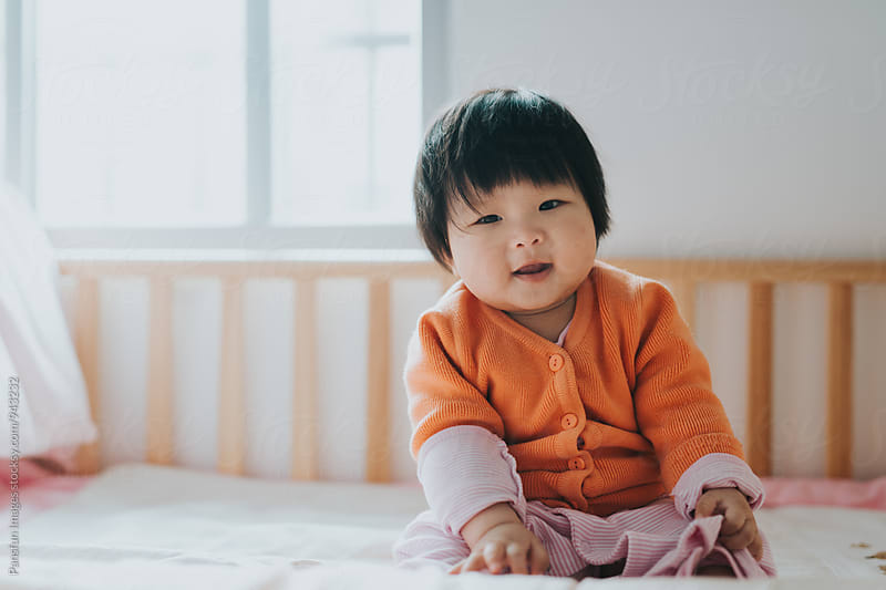 baby girl on bed by Xunbin Pan for Stocksy United