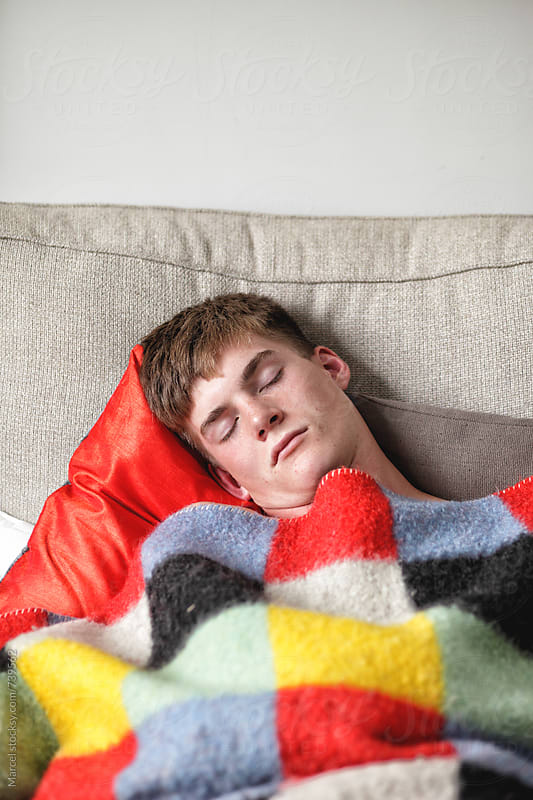 Young man sleeping under a blanket on a couch by Marcel for Stocksy United