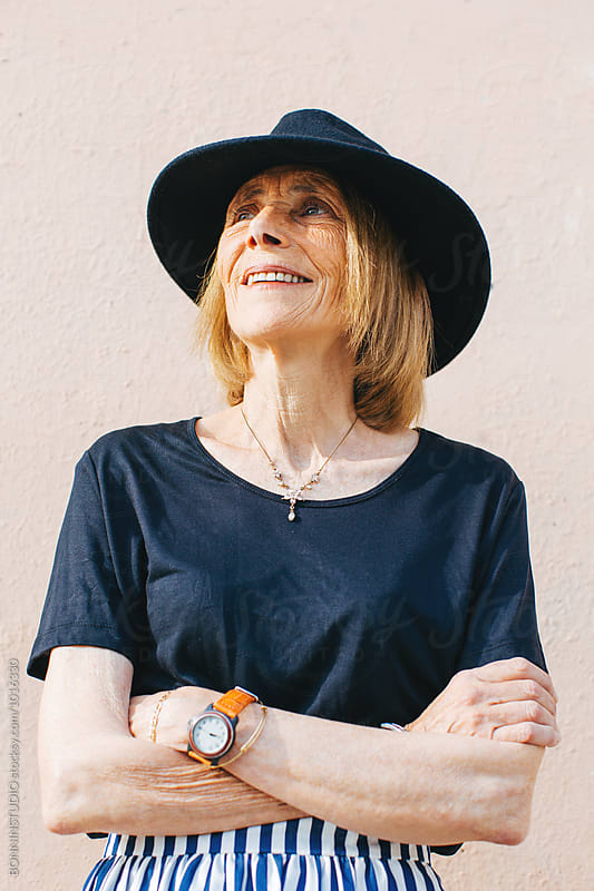 Portrait of a stylish mature woman smiling outside.  by BONNINSTUDIO for Stocksy United