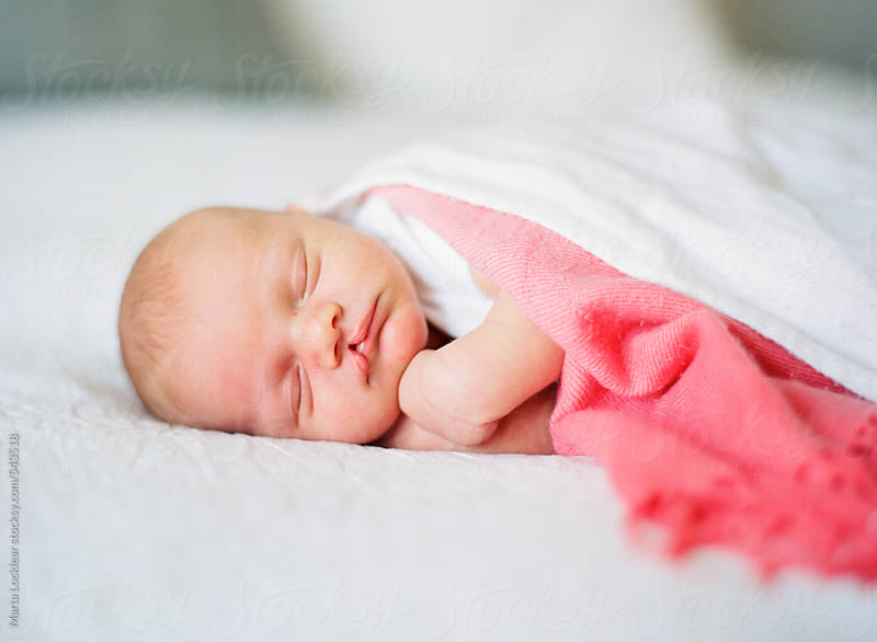 Newborn baby boy with cleft lip sleeping on a bed by Marta Locklear for Stocksy United