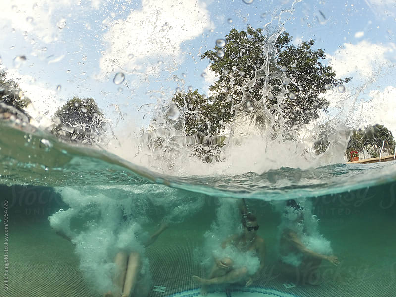 Friends jumping underwater in pool by Guille Faingold for Stocksy United
