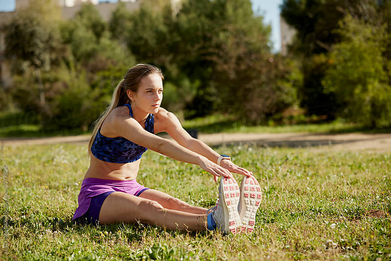 Young Woman Doing Stretching Exercise On Grass by ALTO IMAGES for Stocksy United