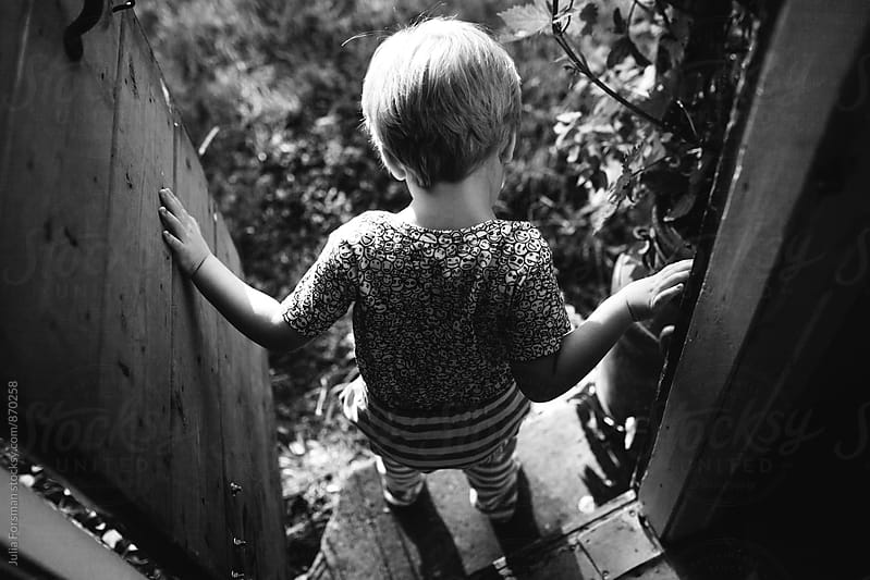 Child emerges from a doorway into a garden. by Julia Forsman for Stocksy United