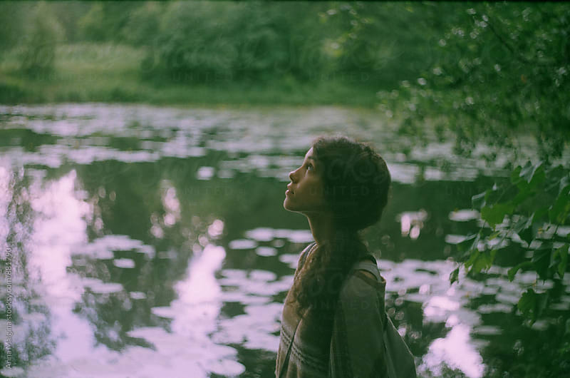 A film portrait of a young beautiful woman in front of lake by Anna Malgina for Stocksy United