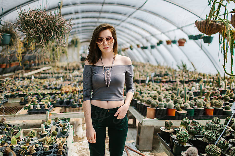 A woman standing in the middle of a cactus greenhouse by Kristen Curette Hines for Stocksy United