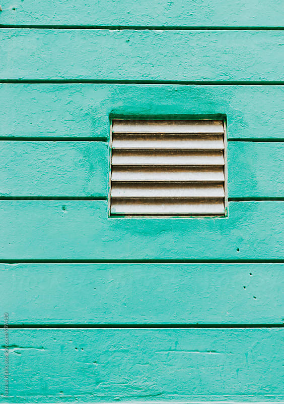 Vent shaft on a green wall by Natasa Kukic for Stocksy United