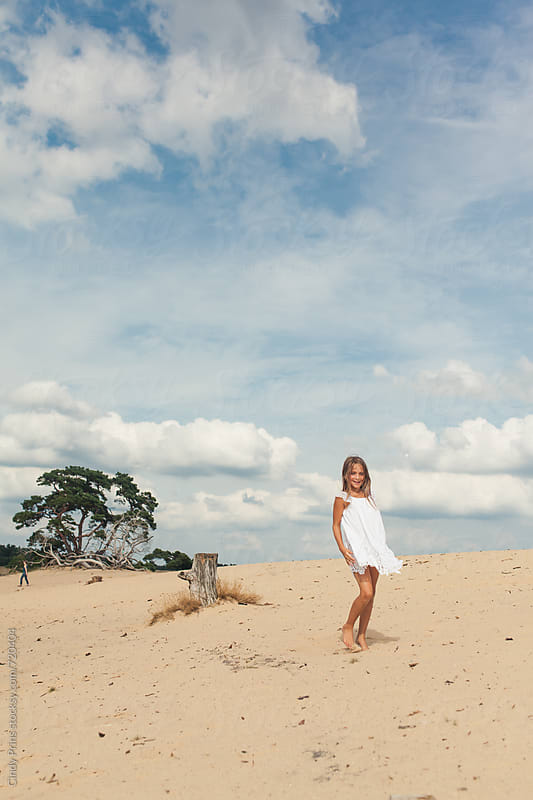 Barefoot little girl in a white dress walking in the sand  by Cindy Prins for Stocksy United