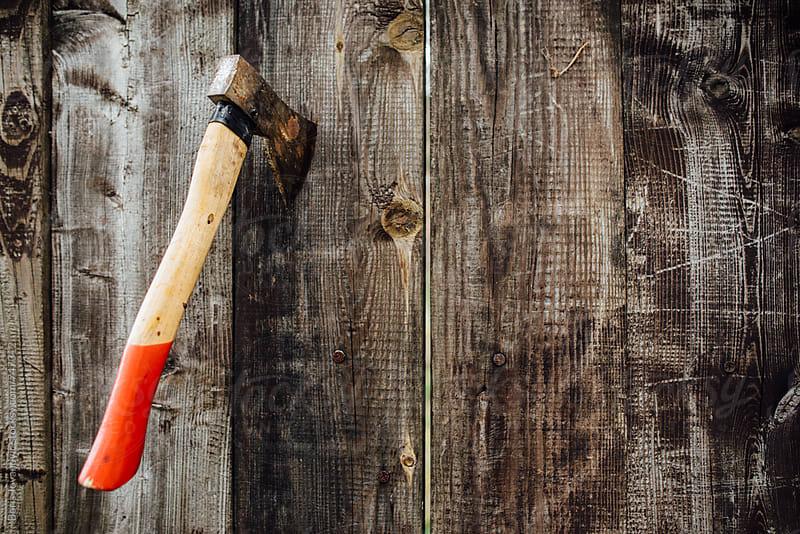 An ax stuck into wood by Boris Jovanovic for Stocksy United