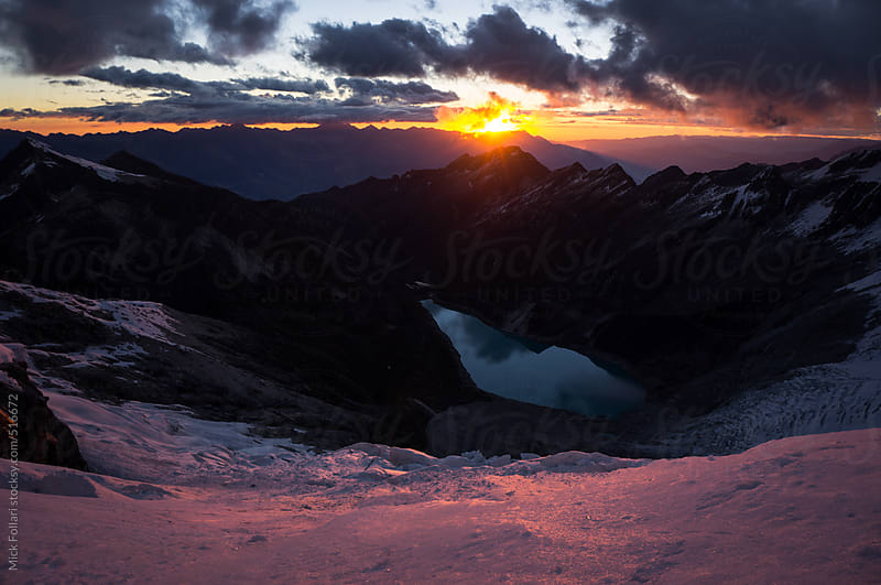 Sunset over the mountains lights up a glacier with rosy light by Mick Follari for Stocksy United