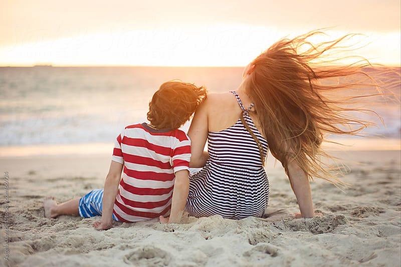 Boy and girl sitting at the beach at sunset by Angela Lumsden for Stocksy United