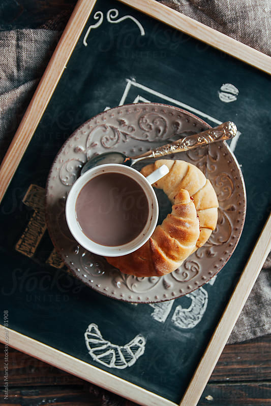 Coffee and croissants on a chalkboard by Nataša Mandić for Stocksy United