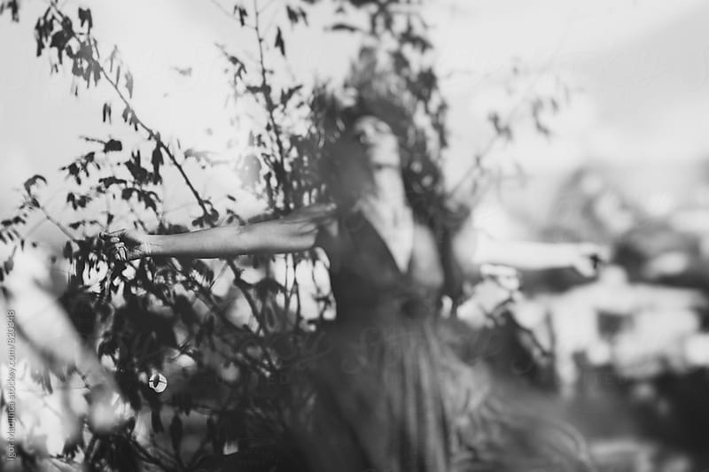 , a pretty woman in a dress in the wind in nature, fantasy, dream by Igor Madjinca for Stocksy United