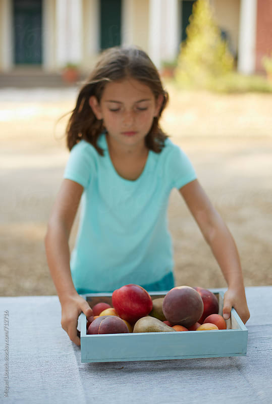 Young girl with a tray full of fresh fruit by Miquel Llonch for Stocksy United