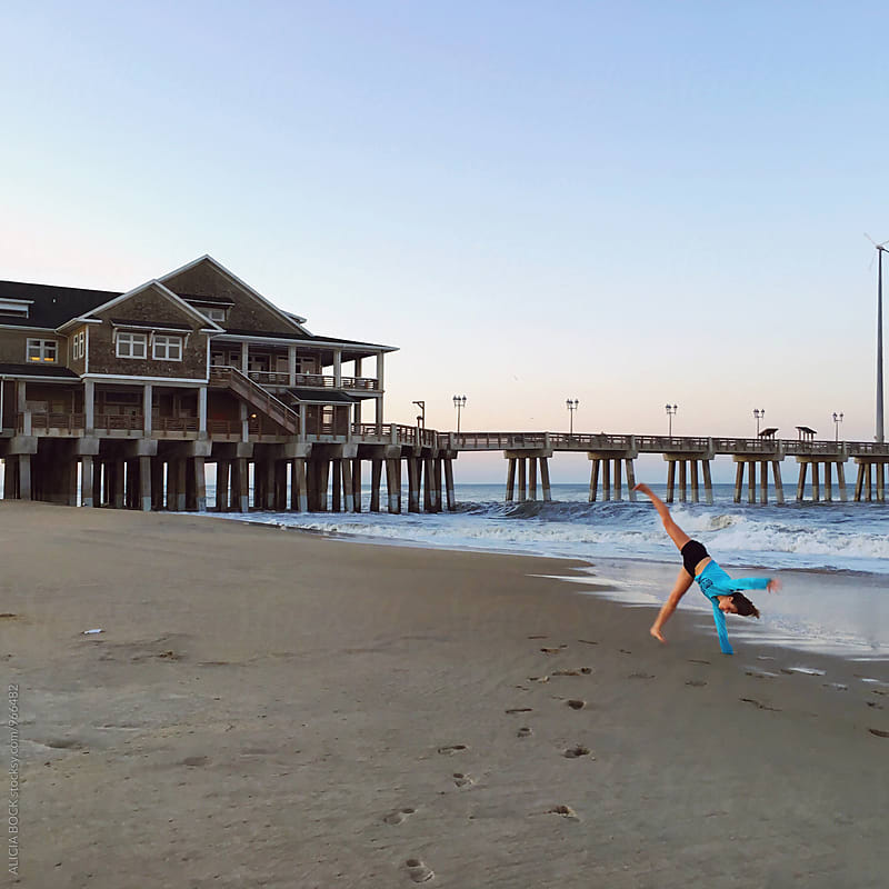 A Teen Girl Doing A Cartwheel On A North Carolina Beach by ALICIA BOCK for Stocksy United