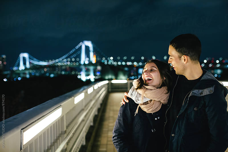 Laughing couple having fun in Tokyo at night. by BONNINSTUDIO for Stocksy United