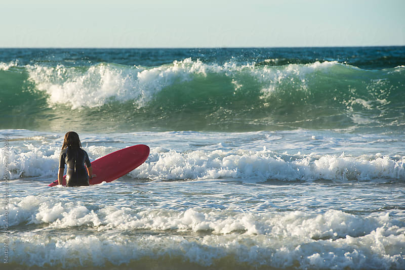 Girl getting in to the water with a red surf board  by Marta Muñoz-Calero Calderon for Stocksy United