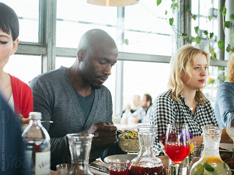 Lunch With Friends - Portrait of Black Man Helping Himself to Food in Bright Restaurant by Julien L. Balmer for Stocksy United