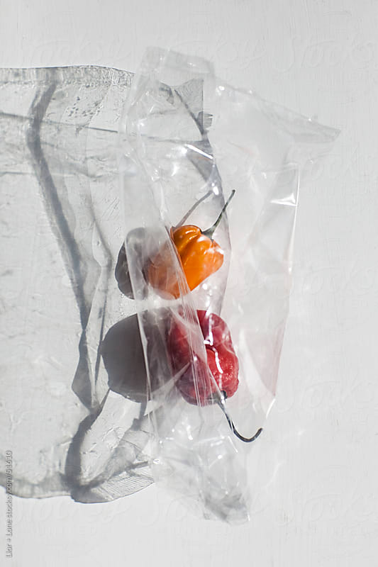 red and yellow habanero chilies in cellophane wrapping by Lior + Lone for Stocksy United