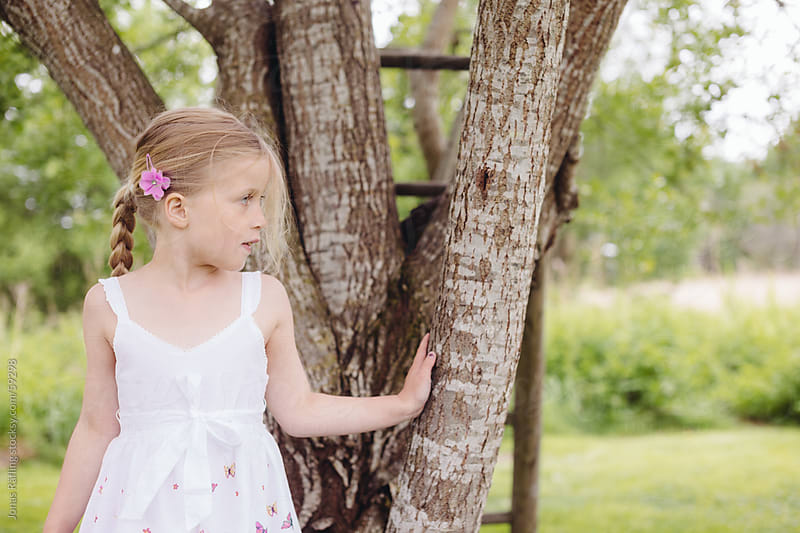 Young girl in a white dress standing at a tree by Jonas Räfling for Stocksy United