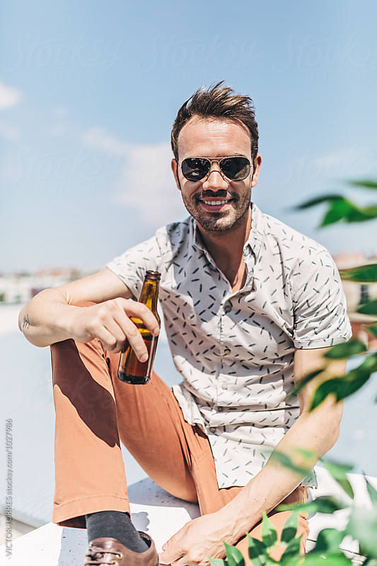Portrait of a Young Handsome Man with a Beer Bottle