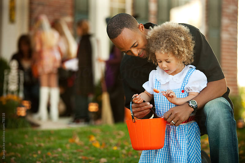 Halloween: Dad and Daughter Look at Halloween Candy by Sean Locke for Stocksy United