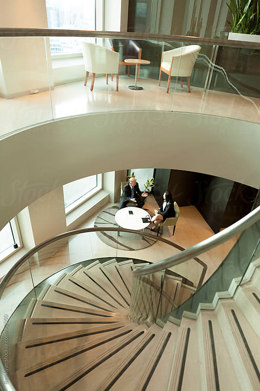 Split level view of foyers with executives in discussion on lowe by Ben Ryan for Stocksy United