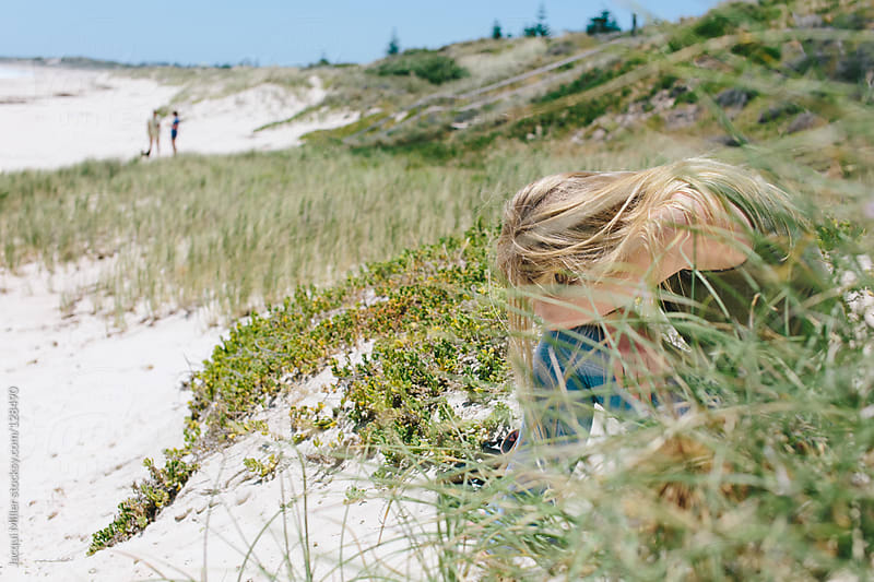 Teenage girl resting beind long grass at the beach by Jacqui Miller for Stocksy United