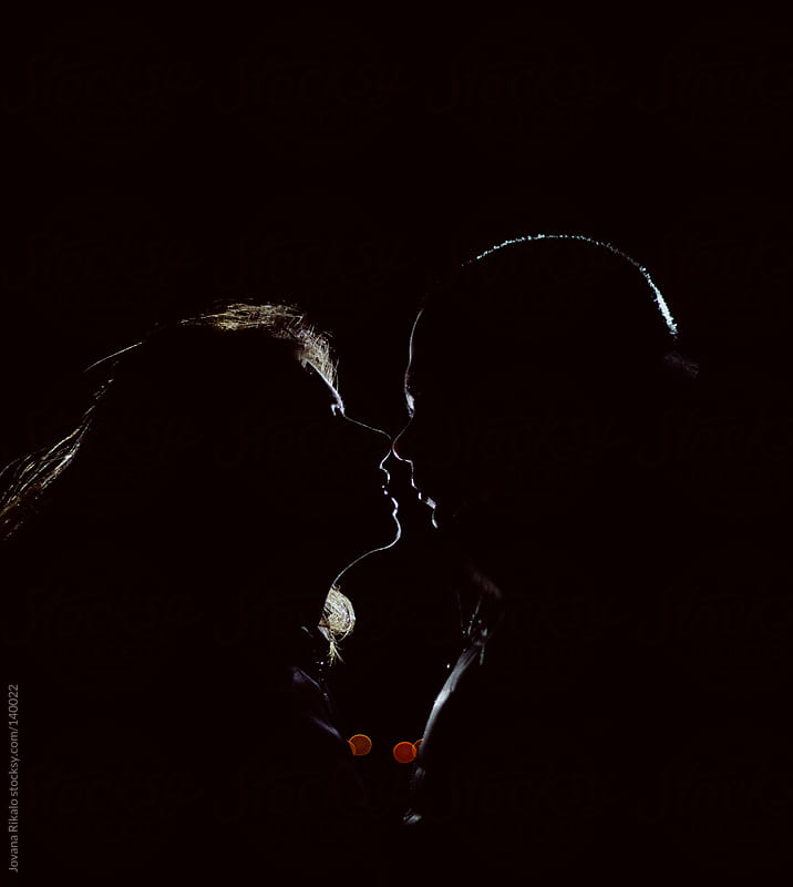 Young couple kissing at night by Jovana Rikalo for Stocksy United
