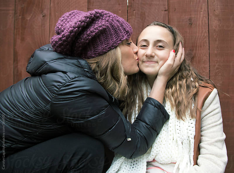 Mother giving her teen (tween) daughter a big, loving kiss by Carolyn Lagattuta for Stocksy United