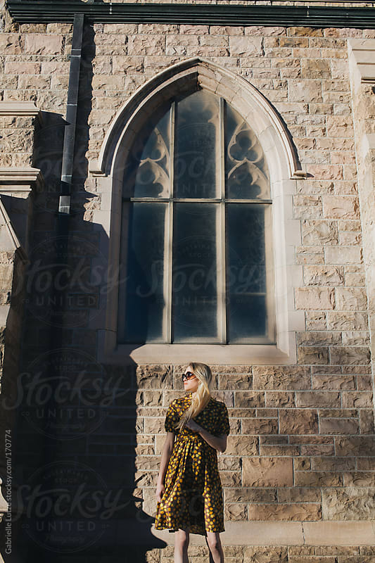 Beautiful Girl in Vintage Dress in front of Church Building by Gabrielle Lutze for Stocksy United