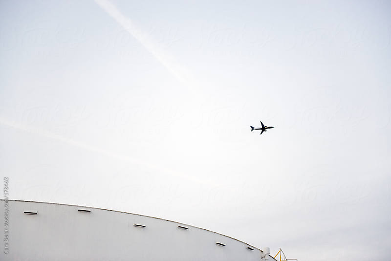 Industrial fuel storage tank with airplane taking off in the distance by Cara Dolan for Stocksy United