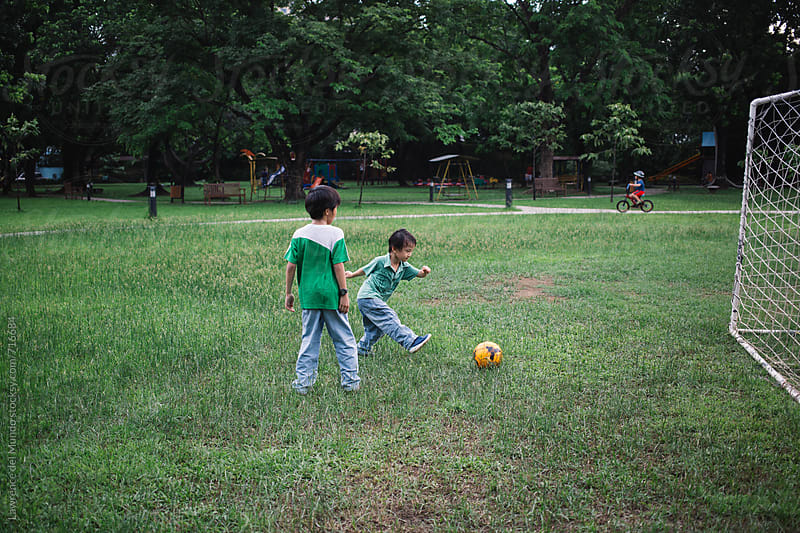Two young brothers playing football in a park on a Sunday by Lawrence del Mundo for Stocksy United