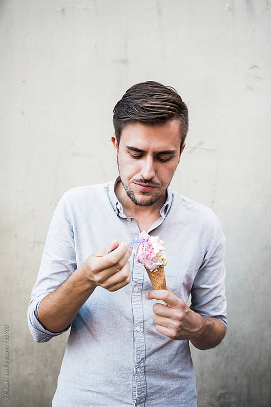Man eating a ice cream by Vera Lair for Stocksy United