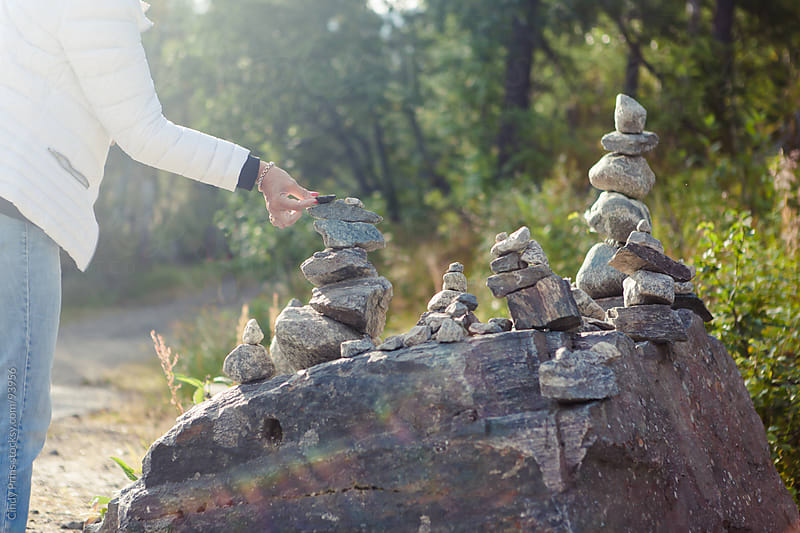 A woman's hand placing a stone on a pile of balancing rocks by Cindy Prins for Stocksy United