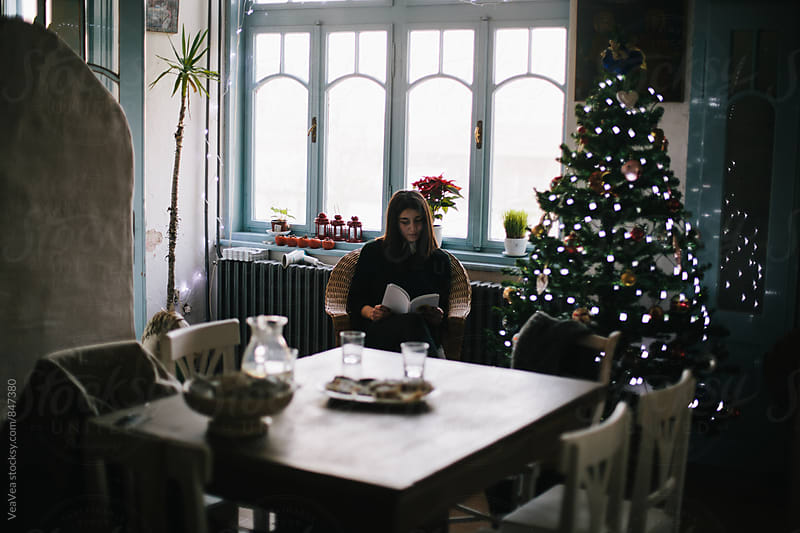 Woman reading a book sitting next to a Christmas tree by VeaVea for Stocksy United