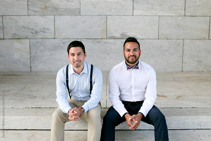Two men sit in front of white marble wall.  by Jen Brister for Stocksy United