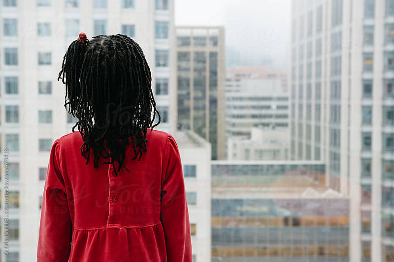 Black girl looking out of a high-rise window in a city by Gabriel (Gabi) Bucataru for Stocksy United