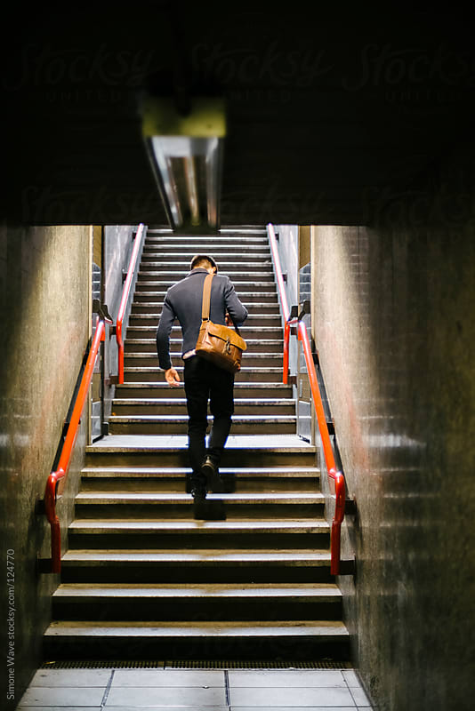 Man climbing the stairs of subway station in Milano by GIC for Stocksy United