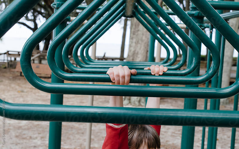 Child plays on the monkey bars at a playground by Cara Dolan for Stocksy United