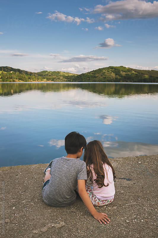 Boy and girl sitting on a dock over a lake by Dejan Ristovski for Stocksy United