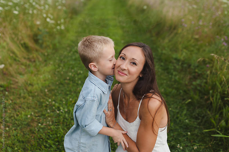 A boy kisses his mothers's cheek, mom looking at camera by Amanda Worrall for Stocksy United