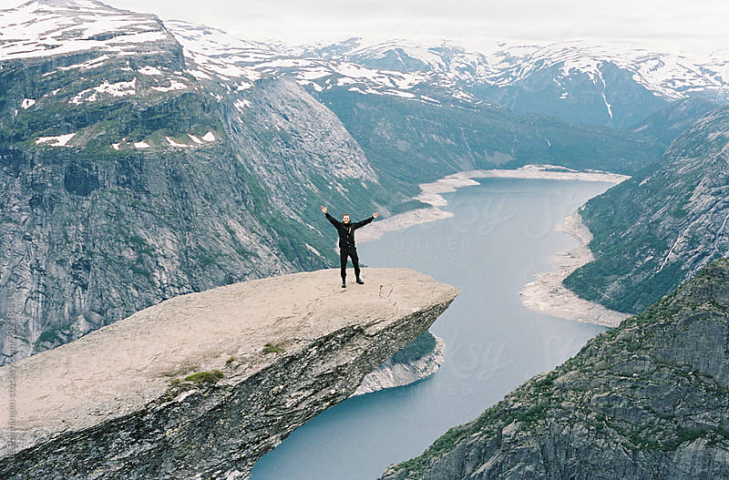 A young hiker reached the edge of Trolltunga in Norway and reaches his hands in the air by Atle Rønningen for Stocksy United