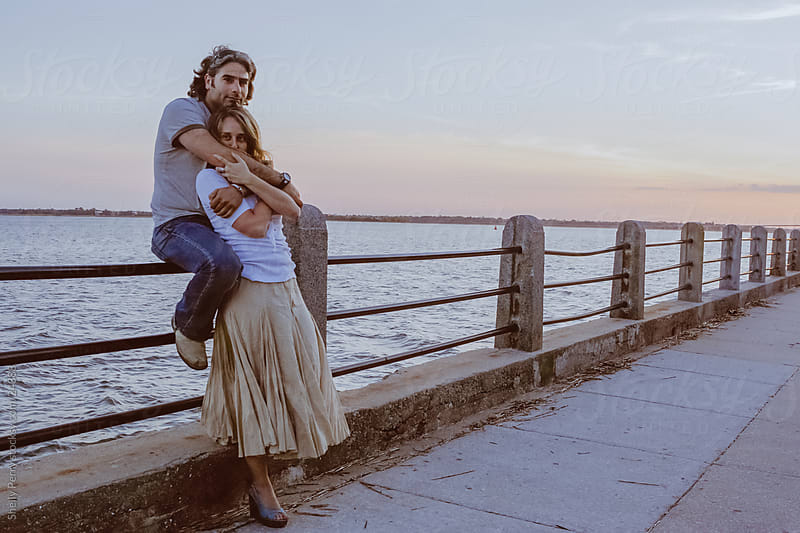 Boardwalk Couple embrace at sunset by Shelly Perry for Stocksy United