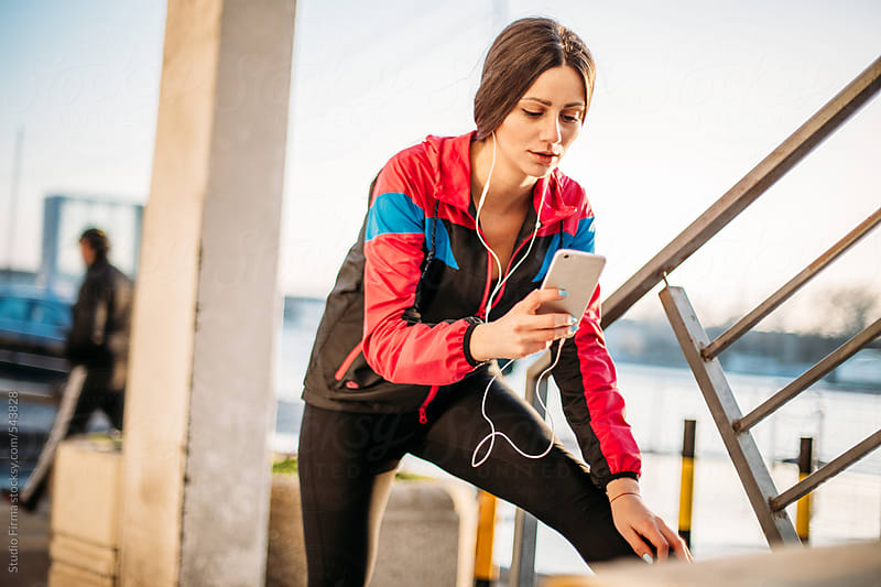 Woman using smart phone while stretching after running. by Studio Firma for Stocksy United