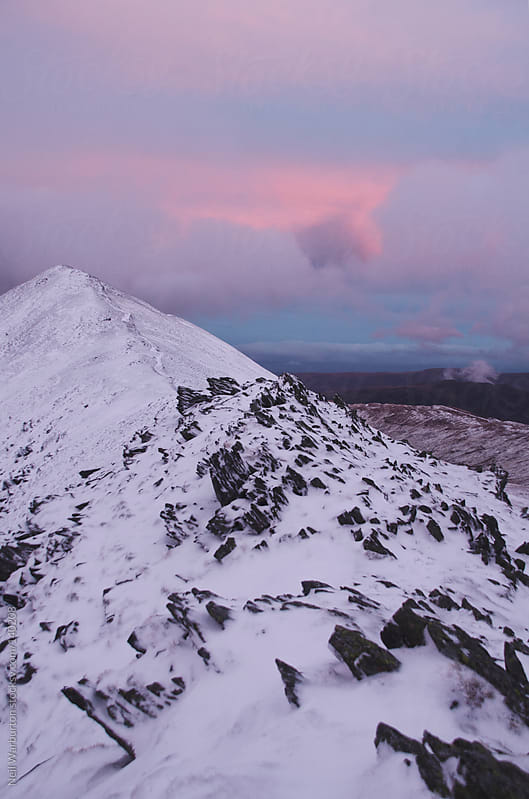 Pink clouds and mountain ridge by Neil Warburton for Stocksy United