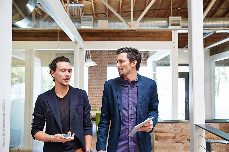 Two millennials having a walk and talk meeting at work by Trinette Reed for Stocksy United