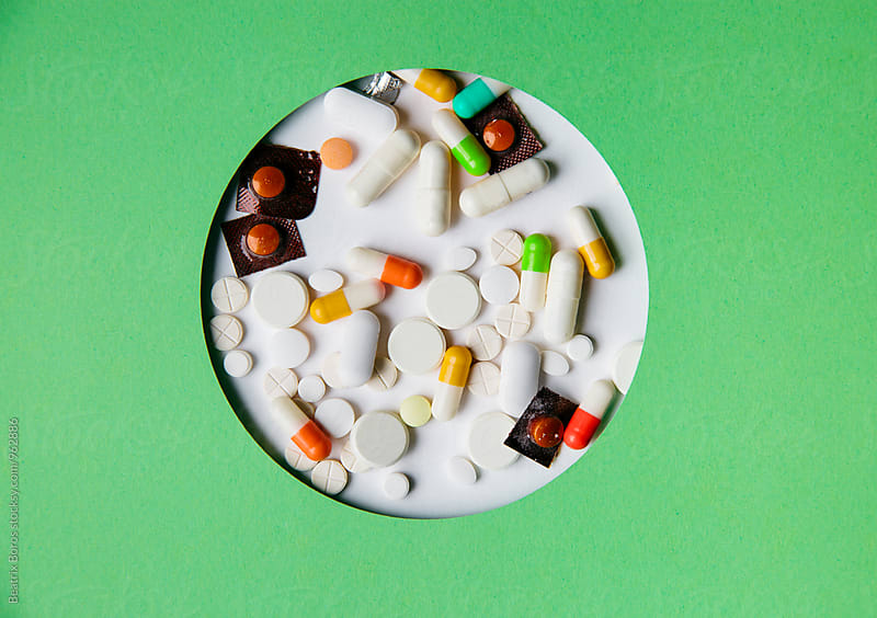 Capsules, pills and medicines in a circular shape with green surface by Beatrix Boros for Stocksy United